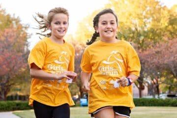Two girls in Girls who Run shirts running